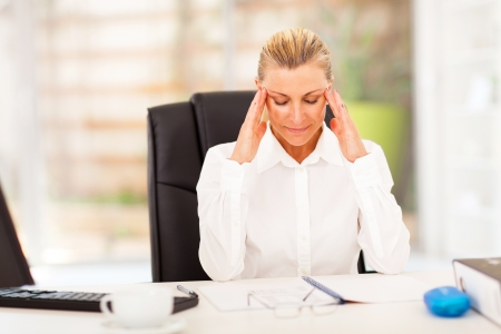elegant female middle aged office worker resting in office photo