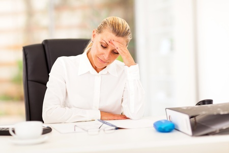 unhappy worker: middle aged businesswoman looking worried when reading sales report