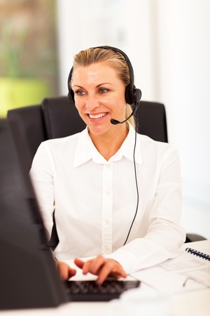 telephonist: happy senior businesswoman with headphones in front of computer