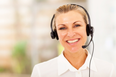telephonist: happy middle aged businesswoman with headphones Stock Photo