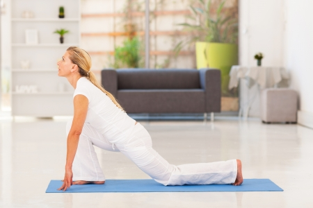 old age home: mature woman doing yoga at home