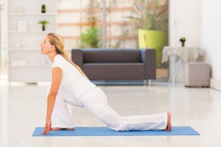 estiramientos: mujer madura haciendo yoga en casa
