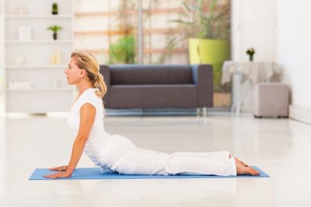 elegant mature lady doing yoga at home photo