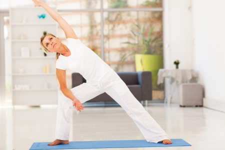 middle aged woman doing fitness workout at home photo