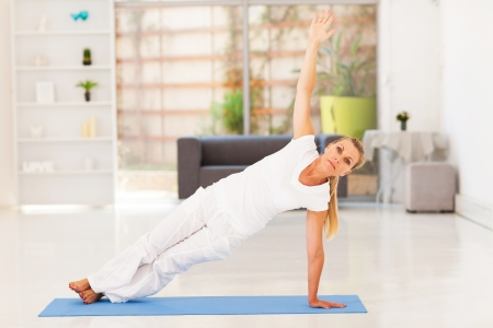 middle aged woman doing fitness exercise at home photo