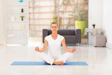 middle aged woman doing yoga meditation at home photo