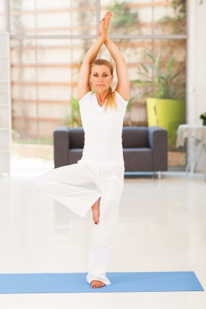casual middle aged woman doing yoga at home photo