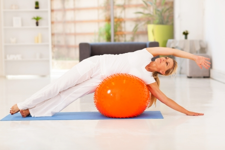 middle aged woman doing fitness on exercise ball at home photo