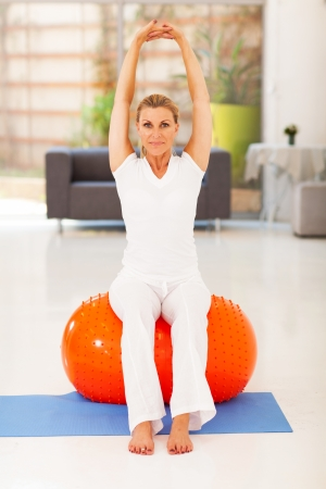 ball stretching: healthy middle aged woman sitting on exercise ball