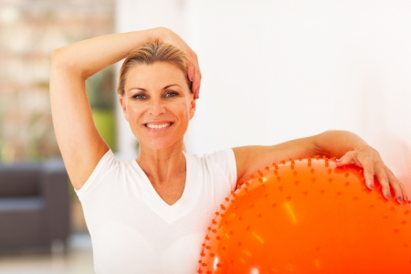 healthy middle aged woman holding exercise ball photo