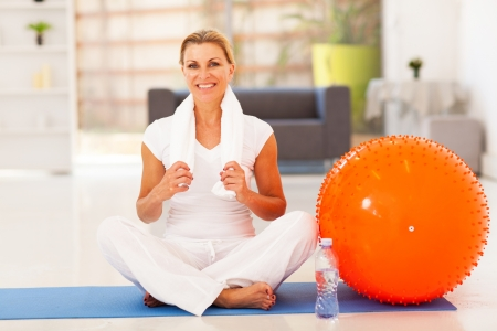 mature woman resting on exercise mat after fitness workout photo
