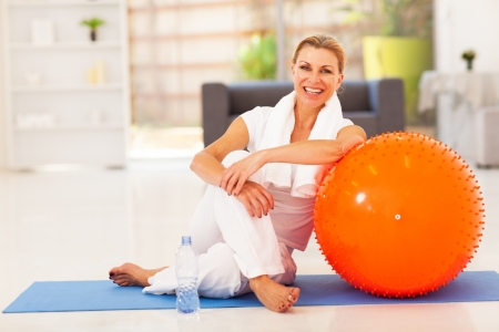 living: happy senior woman resting on mat after exercise at home Stock Photo