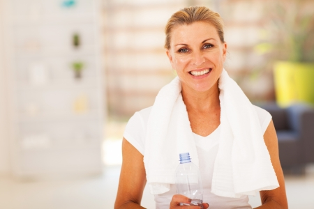 fitness senior woman with towel and water bottle photo
