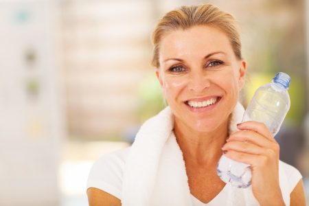 woman in towel: healthy senior woman with exercise towel and water