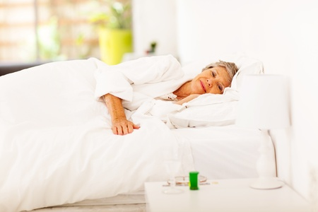 senior woman resting on bed at home photo