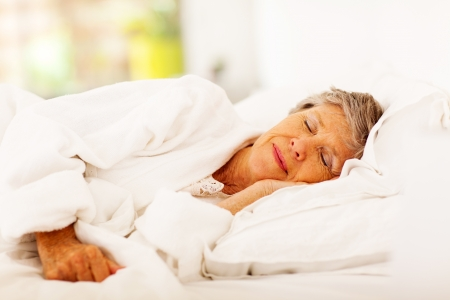 senior woman sleeping on bed photo