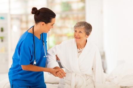 levantandose: casa cuidador ayuda a la mujer mayor de levantarse Foto de archivo