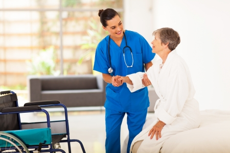 home health care: young female caregiver helping senior woman getting up