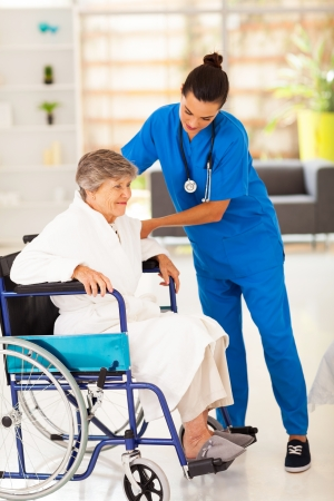 care giver: friendly caregiver helping senior woman on wheelchair Stock Photo