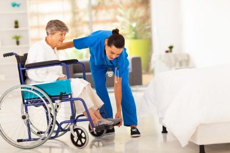 jeune vieux: soignant aidant jeune femme �g�e en fauteuil roulant Banque d'images