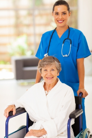 pretty young nurse pushing senior woman on wheelchair