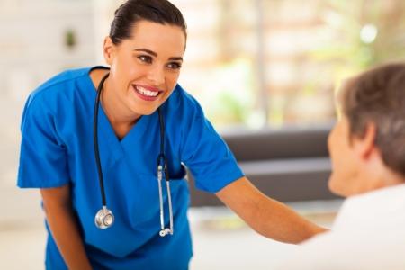80s adult: enfermera amable joven que habla con el paciente mayor en el hospital Foto de archivo