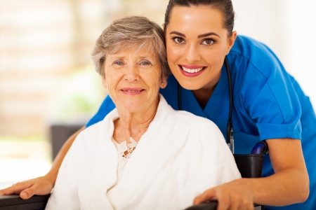 care at home: happy senior woman on wheelchair with caregiver Stock Photo