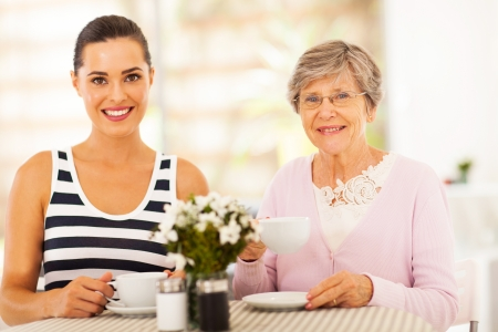 beautiful young woman having tea with grandmother or mother photo