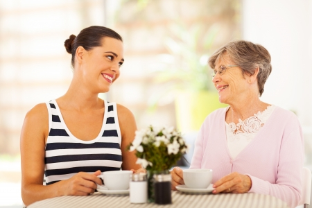 young woman visiting senior mother and having coffee together photo