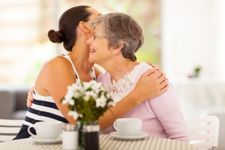 grandma: young woman hugging senior mother when visiting her