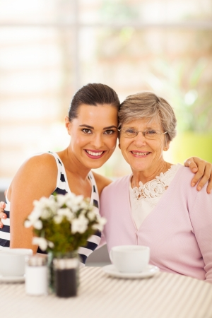 pretty young woman and grandmother having coffee together photo