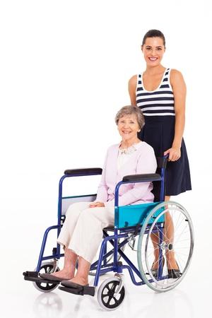 persona en silla de ruedas: hija cuidado empujando madre mayor en silla de ruedas en el fondo blanco Foto de archivo