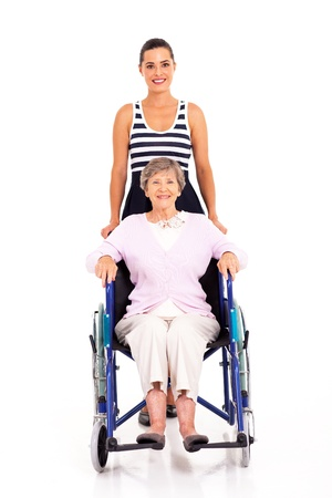 adult granddaughter pushing disabled senior grandmother on wheelchair photo