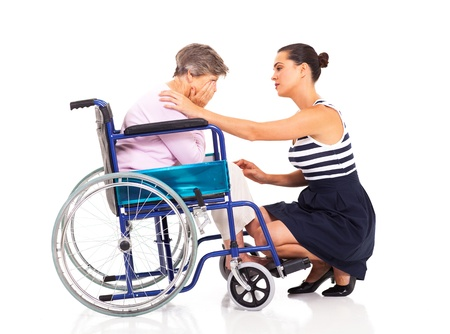 young woman comforting disabled senior mother on white photo