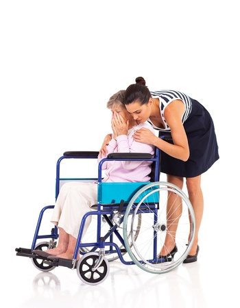 care giver: young female caregiver hugging and comforting lonely disabled senior woman