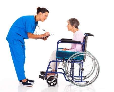 caring nurse helping senior patient filling medical form photo