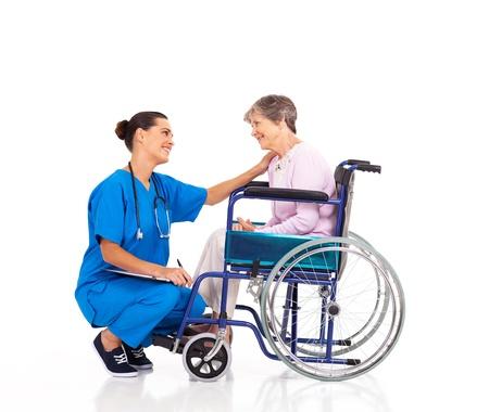 giver: enfermera amable que habla con el paciente incapacitado mayor Foto de archivo