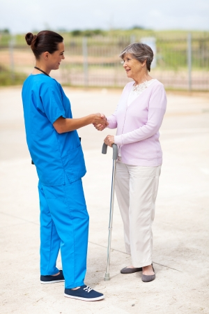 care giver: young nurse in uniform talking to senior woman outdoors Stock Photo