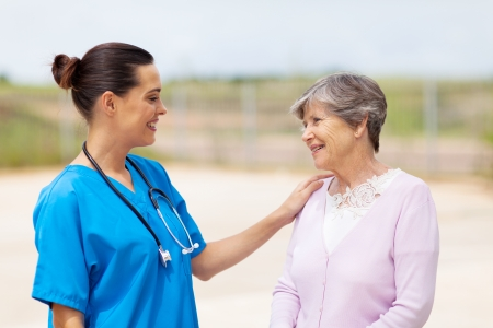 care giver: happy young nurse talking to senior woman outdoors