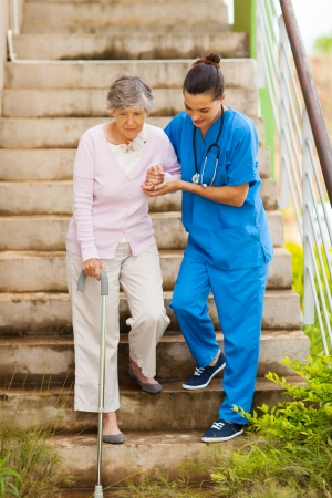 giver: caring nurse helping senior patient walking down stairs