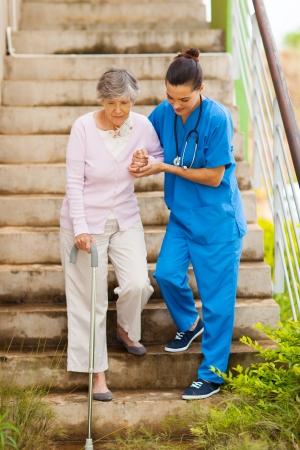 caregiver: caring nurse helping senior patient walking down stairs