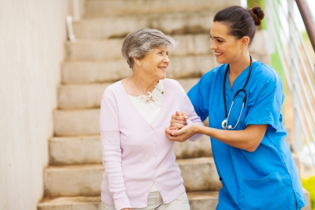 giver: young caregiver helping senior woman walking down stairs