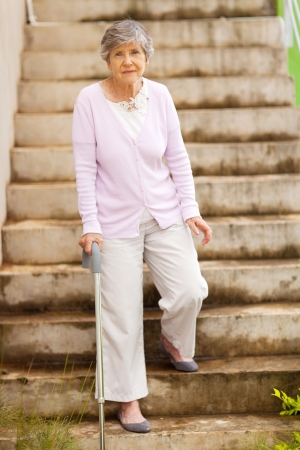 lonely senior woman standing by stairway photo