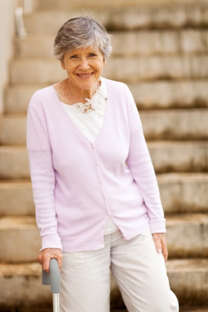 happy elderly lady standing by stairway with cane photo