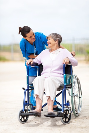 caregiver talking to disabled senior woman outdoors photo
