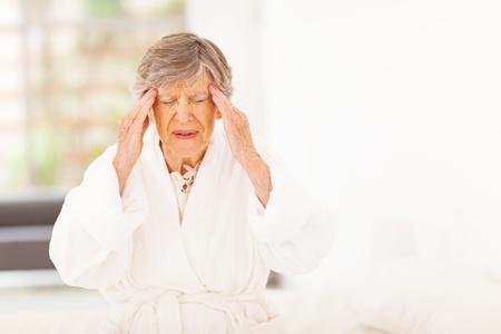 unease: senior woman feeling headache at home