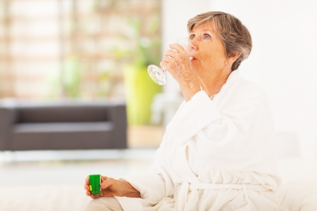 unease: elderly woman drinking medicine at home