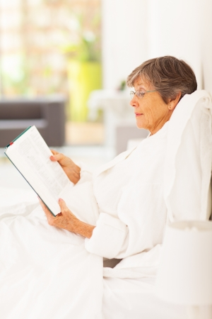 elegant senior woman lying on bed reading a book photo