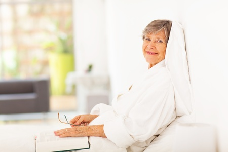 peaceful elderly woman reading book on bed photo
