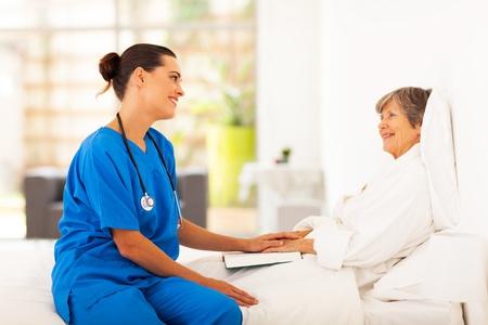 enfermera con paciente: enfermera visitas amistosas paciente que se recupera alto Foto de archivo